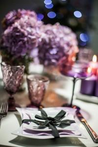 Violetinės spalvos stalo dekoras su juodu kaspinėliu