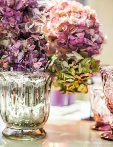 Violetinio stalo dekoro gėlės ir sidabrinės vazos
